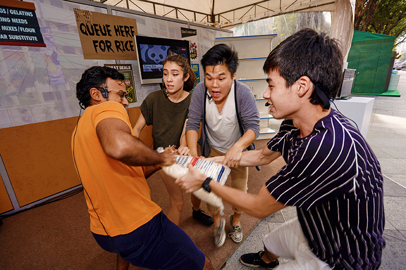 Actors show an extreme scenario of people fighting over food amidst food scarcity at the Climate Change Trail. Photo: WWF Singapore